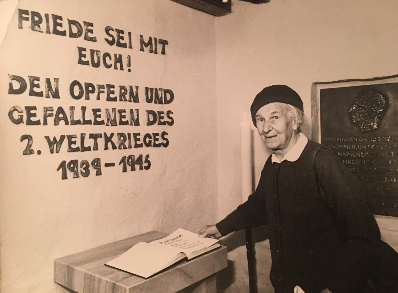6 Tisa von der Schulenburg in der nahegelegenen Gressower Dorfkirche, hinter ihr die Gedenkplatte, die sie für ihren Bruder angefertigt hat.